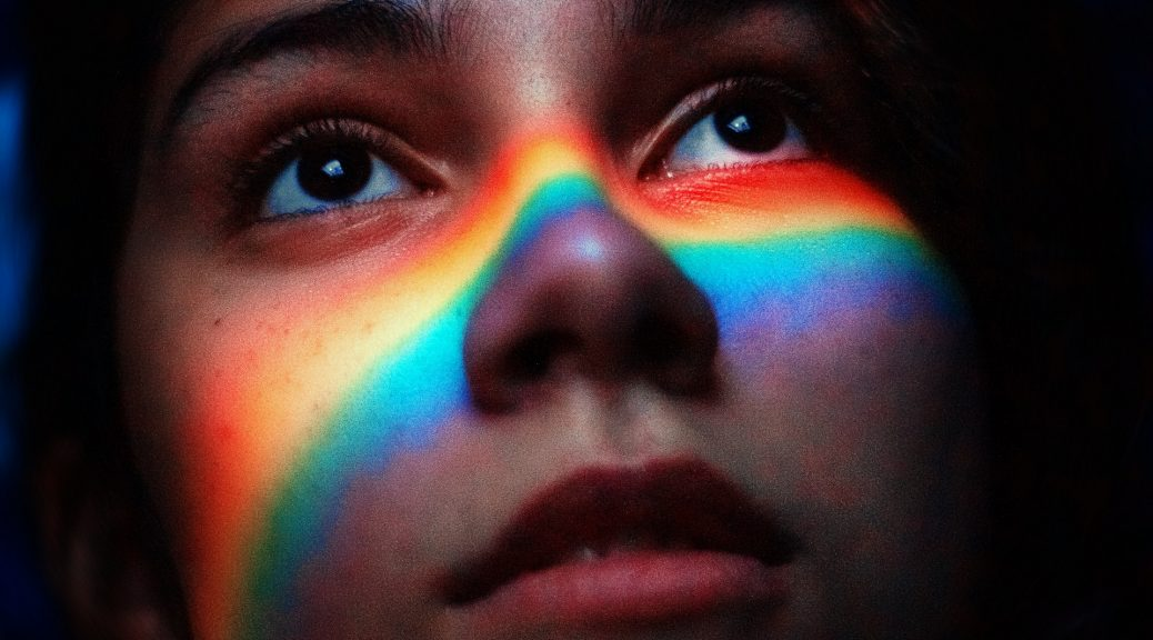 women with rainbow light reflecting on her face